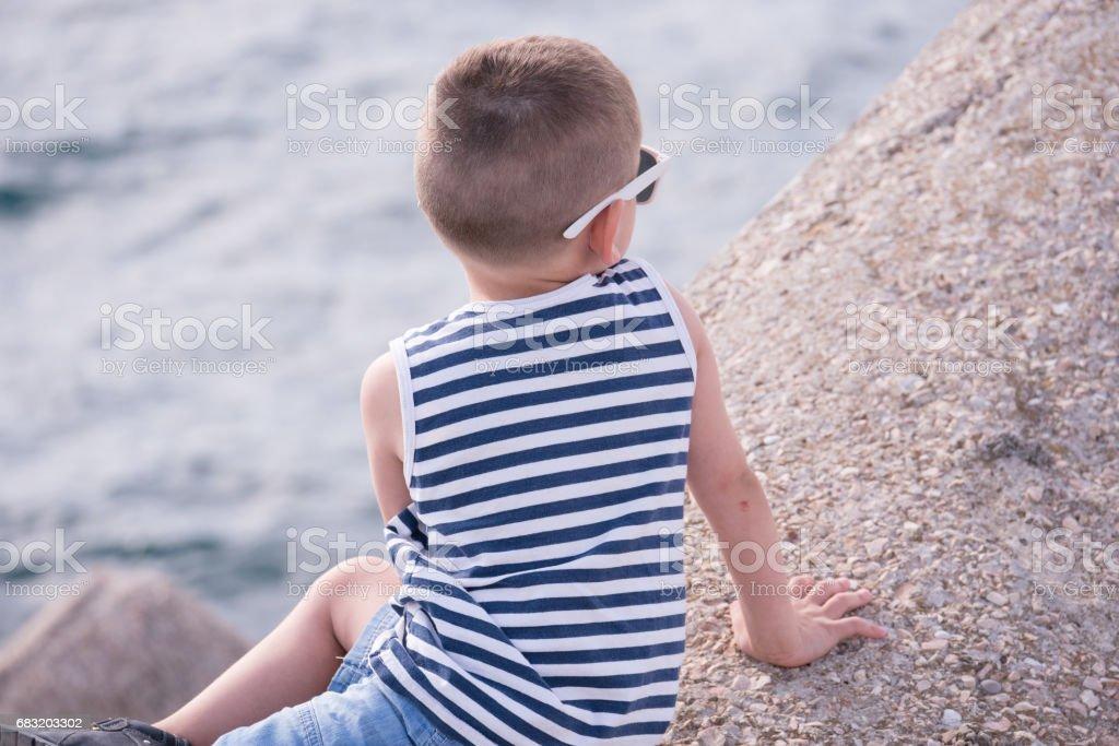 一隻小羊,身穿條紋的襯衫和短褲坐在大海邊 免版稅 stock photo