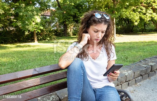 istock One lonely beautiful girl sitting alone and depressed on the bench in the park feeling abandoned and betrayed from her boyfriend when he suddenly break up with her by text message on the phone 1163353115