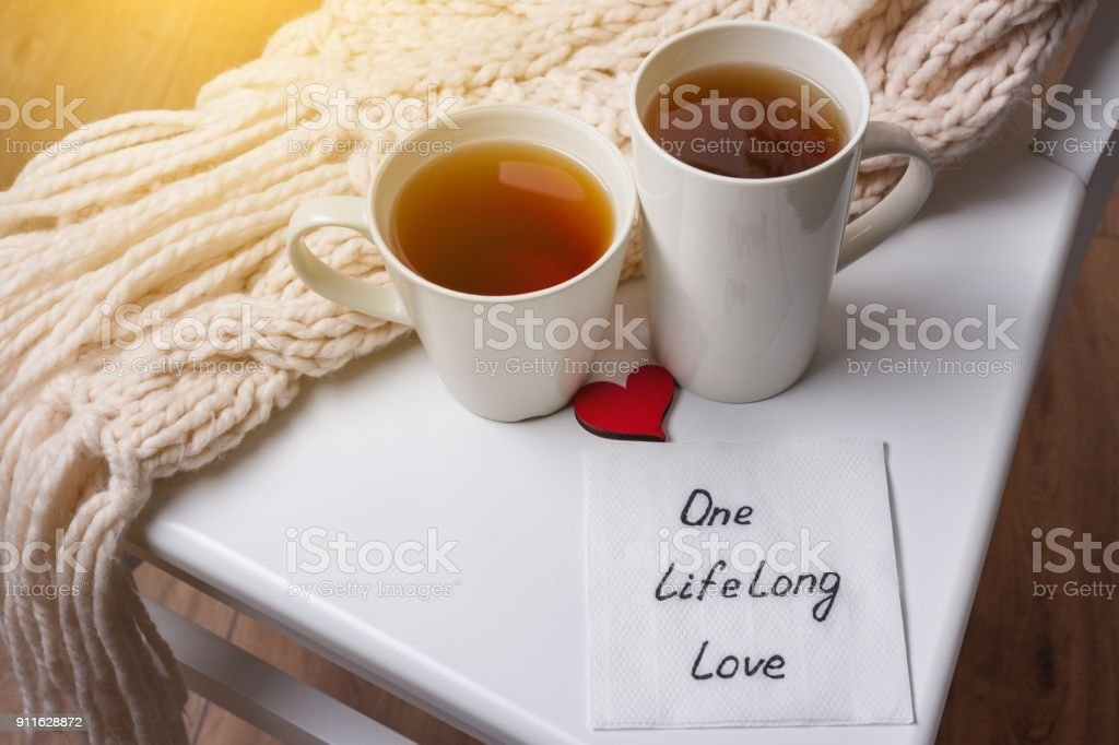 One long life of love is an abstract symbolic image. Couple of cups, background warm scarf, in home interior, napkin with text. stock photo