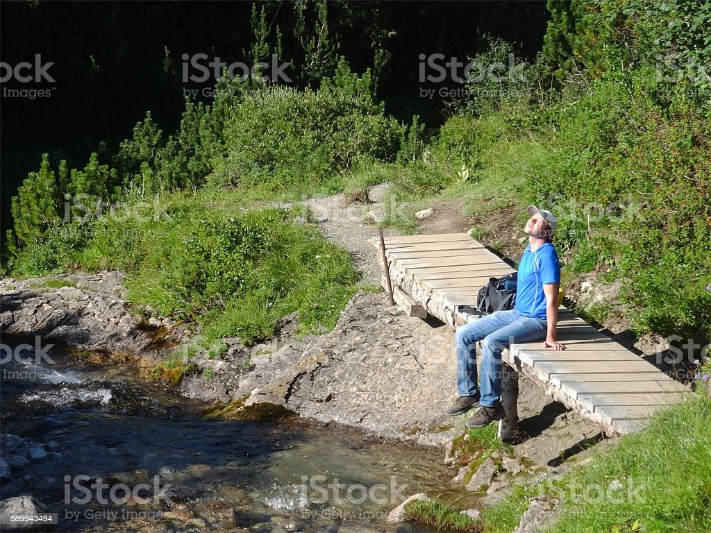 One male hiker rests enjoying the sunshine on his face. stock photo