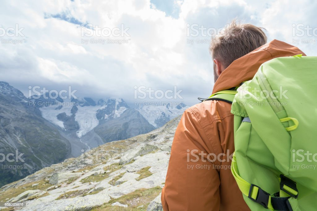 One male hiking in Switzerland looking at mountain view stock photo