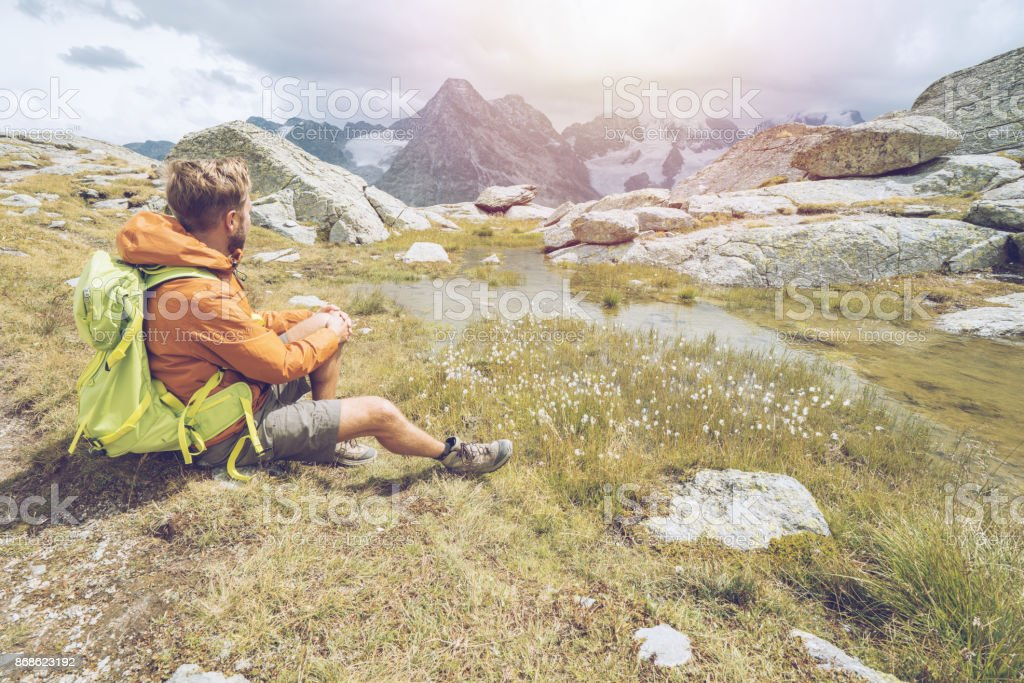 One male hiking in Switzerland ooking at mountain view stock photo