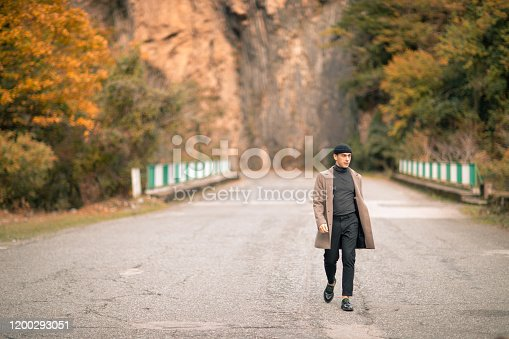 469211680 istock photo One male model dressed with a stylish coat and a fall cap outside 1200293051
