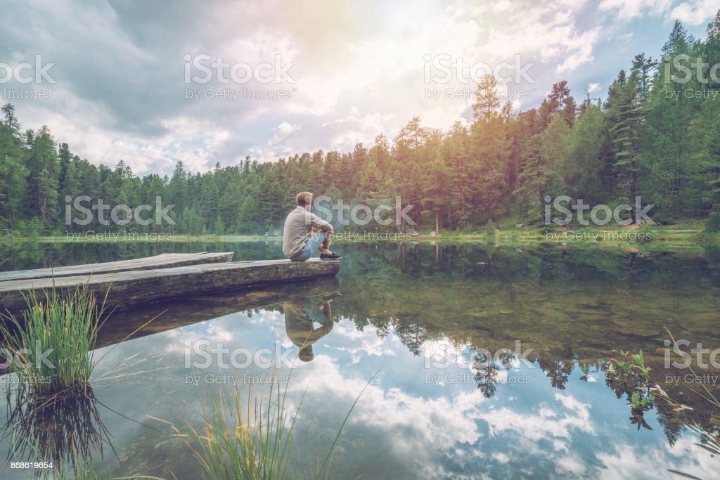 Ein Männchen auf See Pier Blick auf Blick auf die Berge – Foto