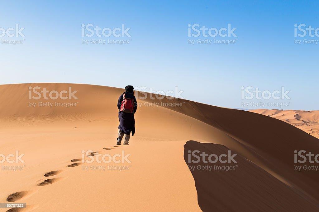 One male tuareg climbing a dune in the desert. stock photo