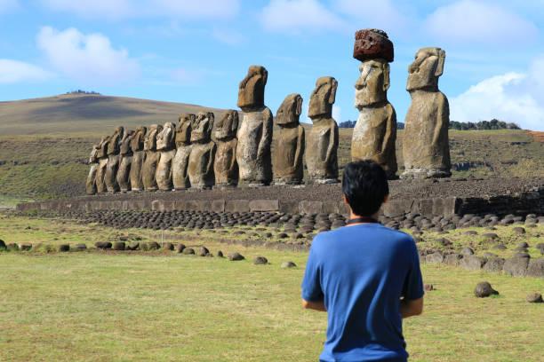 ein mann, bewundern die riesigen moai statuen der ahu tongariki, osterinsel, chile, südamerika - osterinsel stock-fotos und bilder