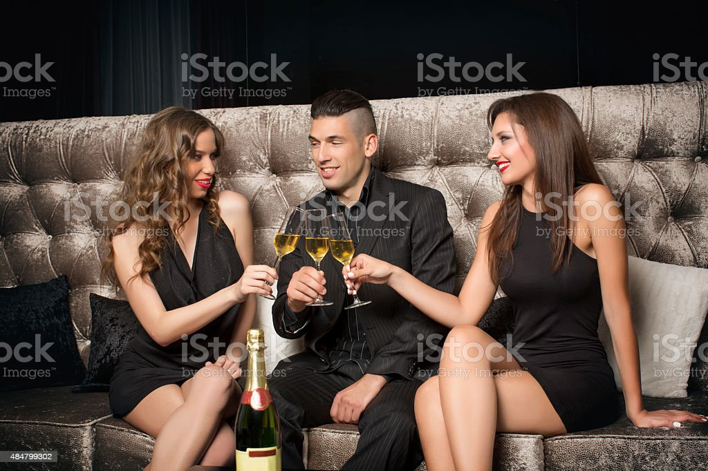 One man and two women celebrating with champagne in nightclub stock photo