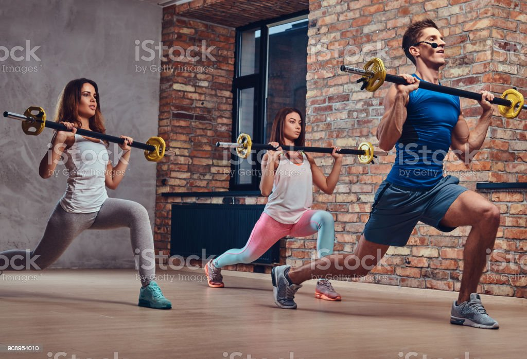 Two fitness women and a coach, stretching squats with barbells in a...
