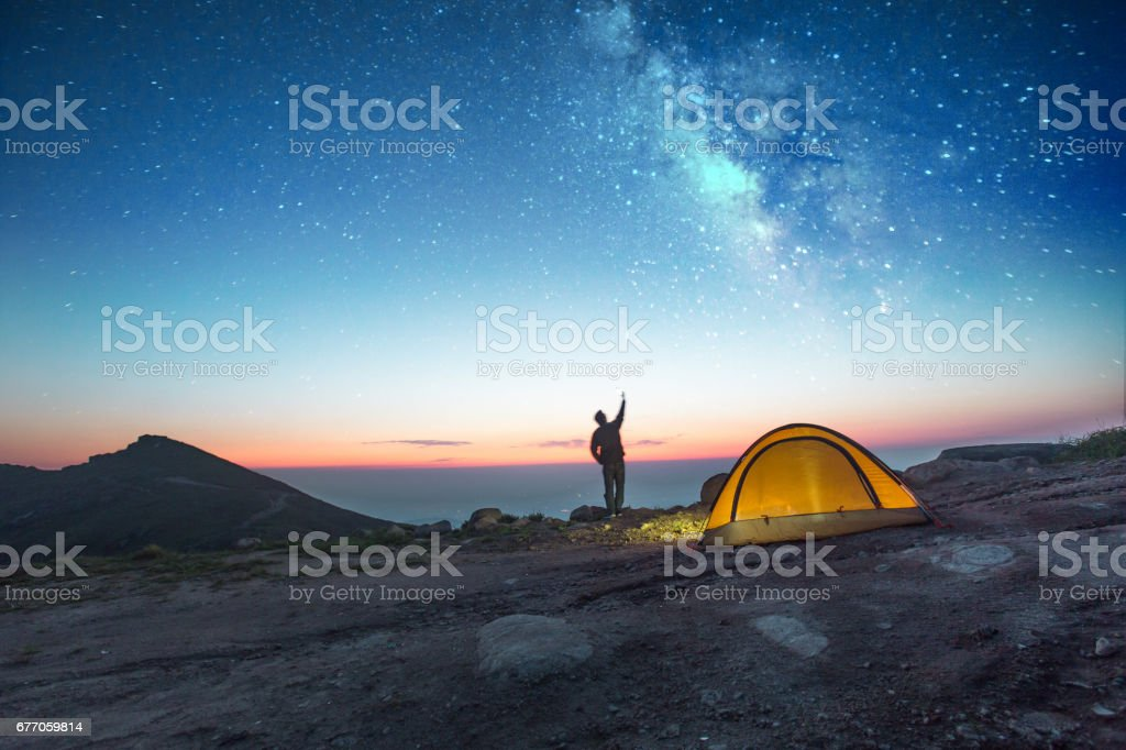 one man camping at night with phone one man camping at night with phone into the sky Adult Stock Photo
