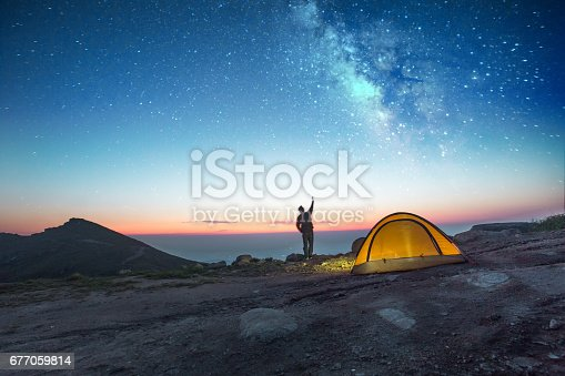one man camping at night with phone into the sky
