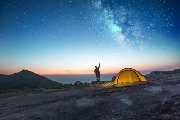 one man camping at night with phone stock photo