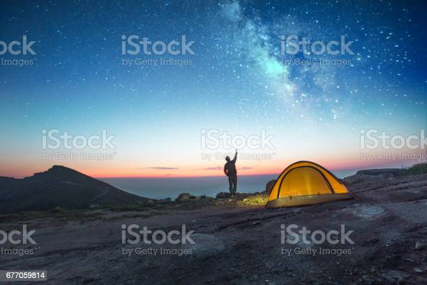 one man camping at night with phone