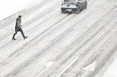 Belgrade, Serbia- January 26, 2019: One man crossing the street outside of crosswalk during the snowstorm and a driving car, high angle view