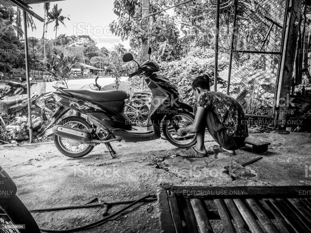E Man Crouching With Moped Koh Lanta Thailand Stock