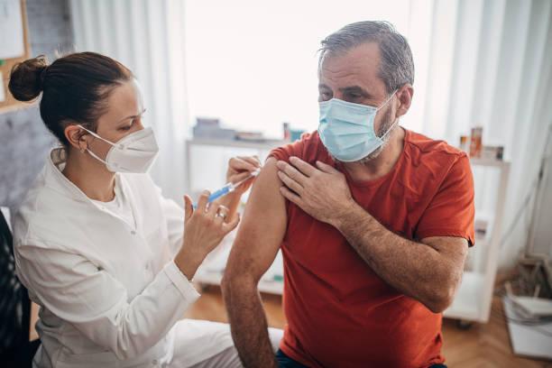 One man getting a coronavirus vaccine stock photo