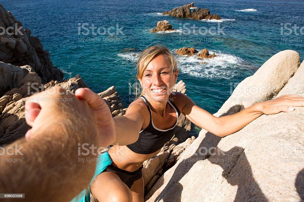 One man helping woman climbing rocks on beach, Italy stock photo