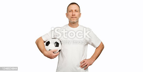 One man holds a soccer ball in akimbo posing.