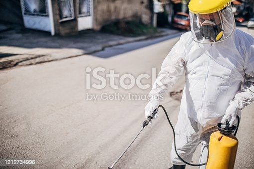 One man in protective suit disinfecting outdoors and spraying the contaminated street