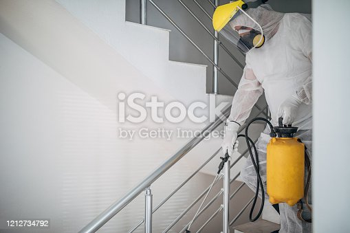 One man in protective suit spraying the house , and disinfecting the staircases