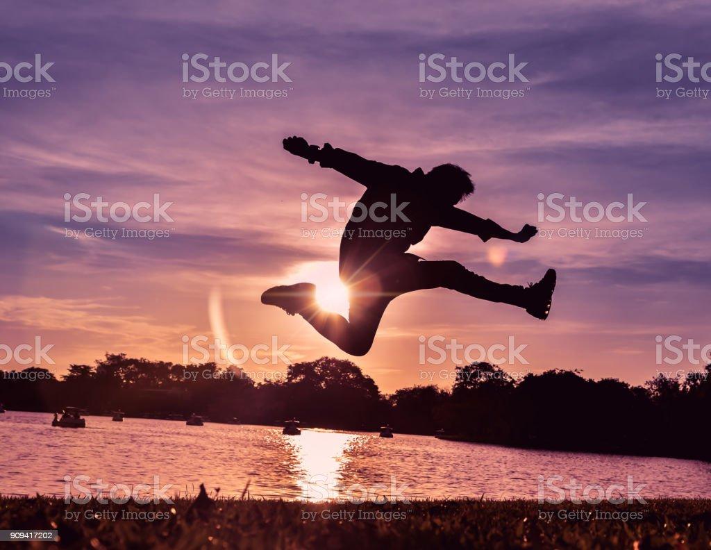 Ein Mann springt in die Luft, er ist sehr glücklich im Leben mit Sonnenuntergang im Hintergrund. Silhouette-Bild – Foto