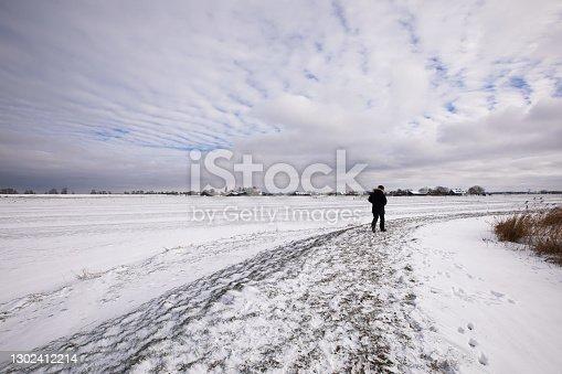 istock One man is walking on a snowy frozen dike in the winter Dutch countryside 1302412214