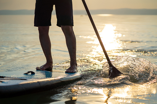 one man legas only on paddleboard in sunset