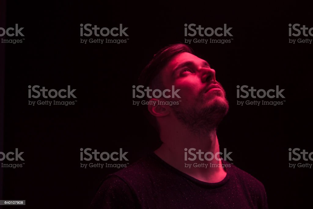one man looking above up, red color light stock photo