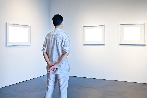 Ein Mann schaut ein weißen Rahmen in Kunstgalerie – Foto