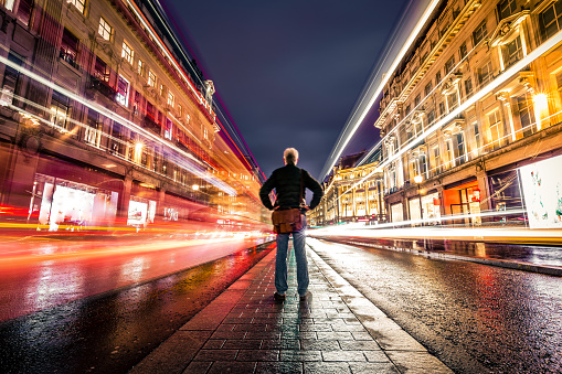 Wide angle color image depicting a rear view of one man standing in the middle of a busy street in central London illuminated at night. The man is surrounded by blurred motion of traffic light trails on both sides of the road. The man is on his own and there are no other people in this busy city street, due to the long exposure used. The man is in his 50s or 60s and is wearing casual clothing - blue denim jeans, a green jacket and a brown leather messenger bag.