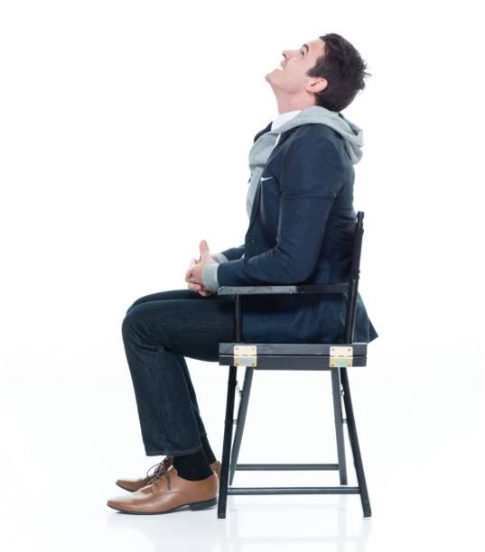 Nur ein Mann / eine Person / volle Länge / Seitenansicht / Profilansicht / Blick nach oben 20-29 Jahre alt erwachsene stattliche Menschen kaukasischen männlich / junge Männer Geschäftsmann / Geschäftsmann sitzt vor weißem Hintergrund im Büro / Direk – Foto