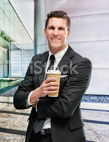 One man only / one person / waist up / front view of handsome people male / young men businessman / business person who is outdoors wearing businesswear who is smiling / happy / cheerful and holding coffee cup / usa / building exterior / california / city / city life / downtown district / financial district / southern california / urban skyline / skyscraper / sunset / sunrise - dawn