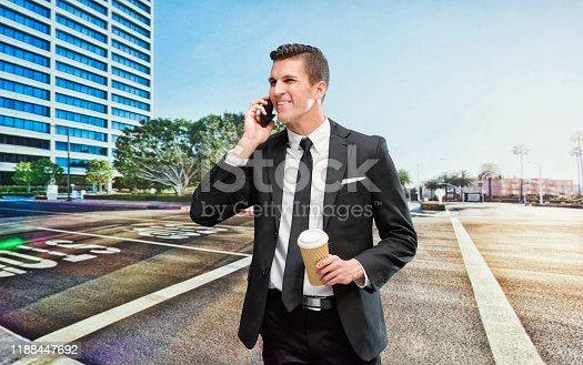 One man only / one person / waist up / front view of young men businessman / business person who is outdoors wearing businesswear who is smiling / happy / cheerful / talking and holding coffee cup / mobile phone / usa / using smart phone / building exterior / california / city / downtown district / financial district / southern california / urban skyline / skyscraper / sunset / sunrise - dawn