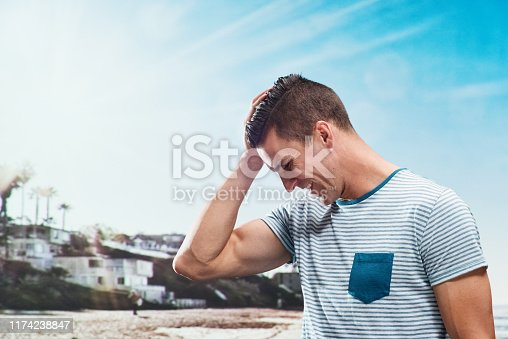 One man only / waist up / side view / profile view / looking down of 30-39 years old adult handsome people / short hair caucasian male / young men standing in front of landscape - scenery / nature / non-urban scene / scenics - nature who by the beach / bay of water / coastline / sand / sea who is outdoors / on vacations wearing t-shirt / shirt who is excited / happy / smiling / successful / shouting / cool attitude and celebration / sky / thank you - phrase / hand in hair