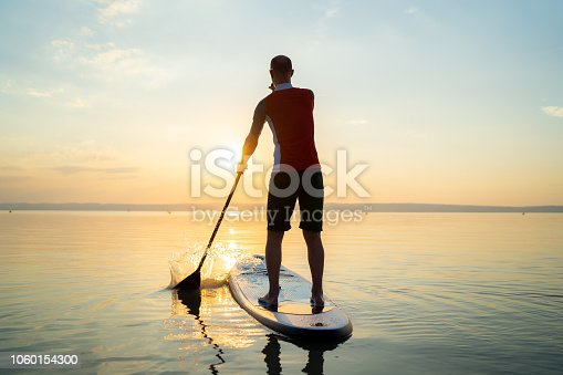 rear view man on stand up paddle board paddling on lake in summer sunset back light
