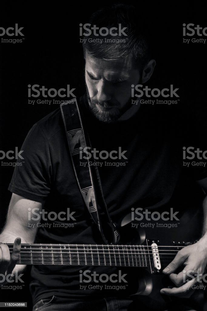 one man, playing guitar, dark and moody rock musician. Dark and moody...