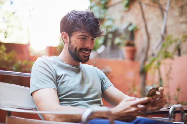 Ein Mann entspannt sich auf der Terrasse zu Hause mit einem Smartphone. – Foto