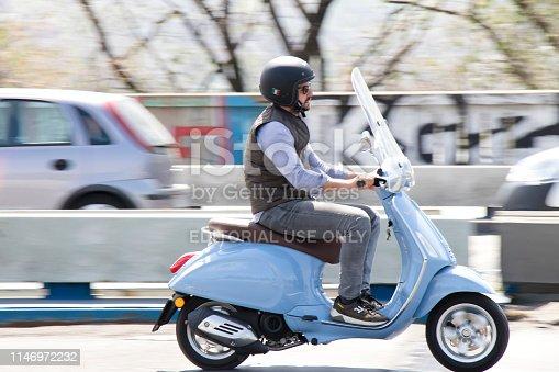 Belgrade, Serbia - April 25, 2019: One man riding light blue vespa scooter over the bridge in city street traffic