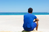 Portrait from back of one man sitting alone at the beach