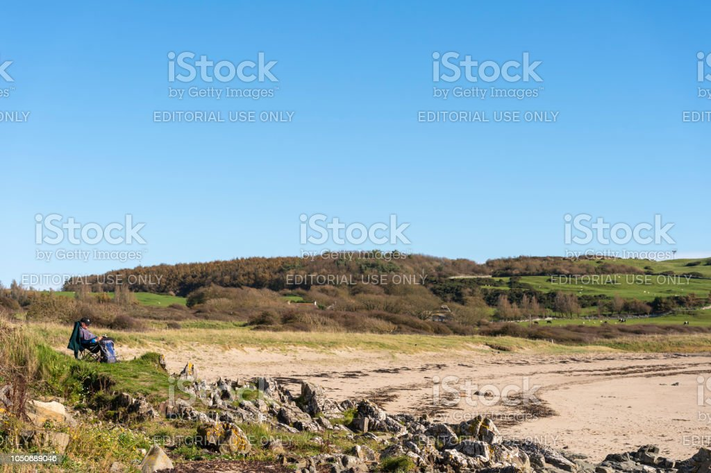 One man sitting reading at the beach stock photo