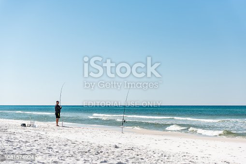 istock One man standing fishing with rod on beach during sunny day in Florida panhandle gulf of mexico with ocean waves, landscape, white sand 1081574924