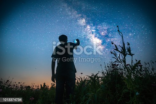 one man standing in the wild looking forward with smart phone on hand shotting photos