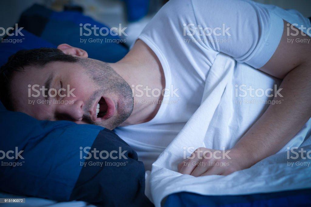 One man suffering of sleep apnea and snoring stock photo