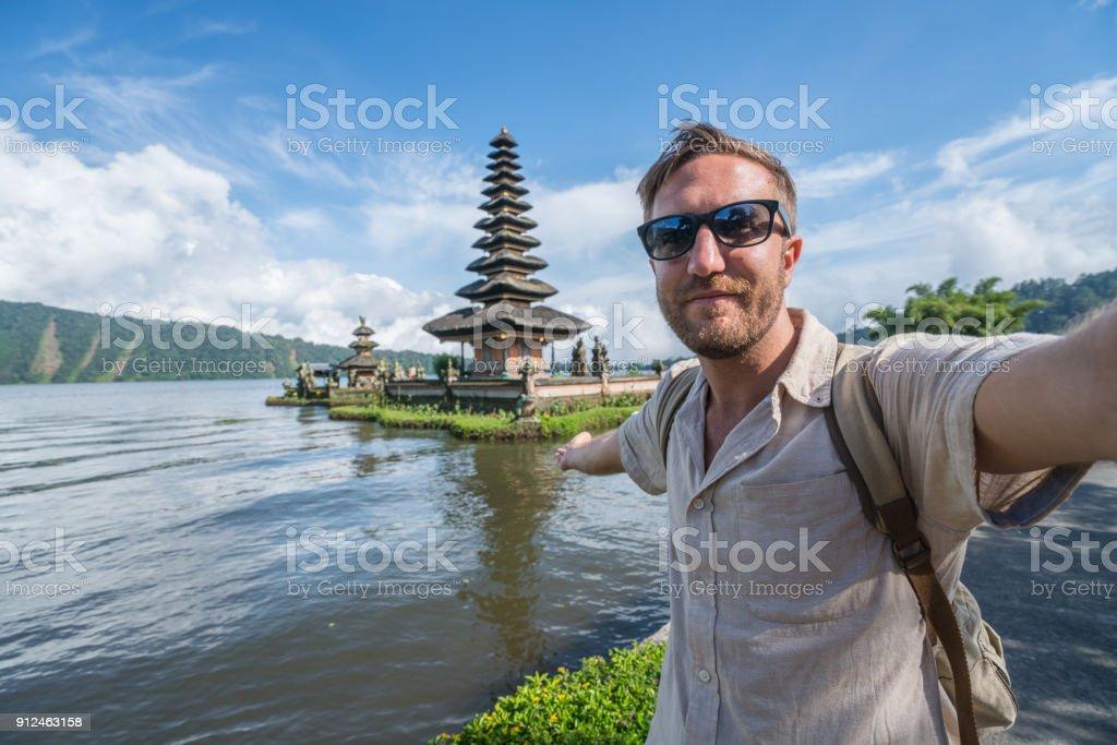 Ein Mann nimmt Selfie mit antiken Tempel in Bali, Indonesien – Foto