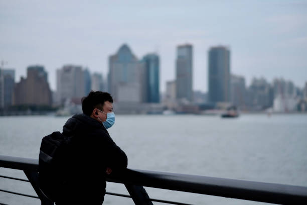 One man wearing surgical mask leaning on balustrade at the bund in China Shanghai/China-March.2020: Coronavirus 2019-nCoV pneumonia in Wuhan has been spreading into many cities. One man wearing surgical mask leaning on balustrade at the bund in China huangpu district stock pictures, royalty-free photos & images