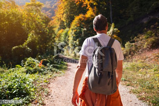 One Caucasian man hiking in the forest. Wearing a backpack and walking on the trail in autumn day.