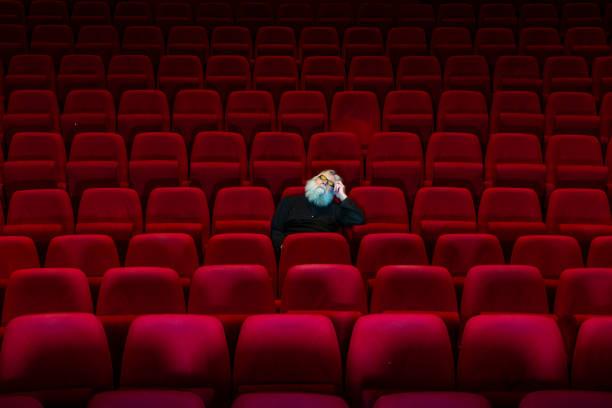 Ein Mann mit weißem Bart sitzt im leeren Kino oder Theater mit bequemen roten Sitzen, schlafen – Foto