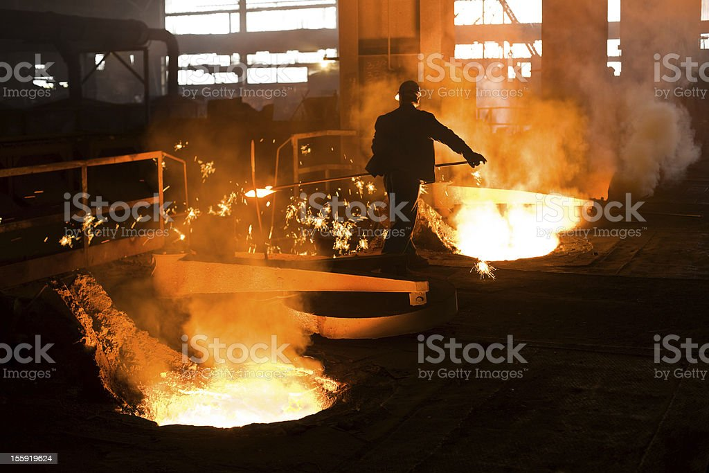 One man working in a fiery foundry stock photo
