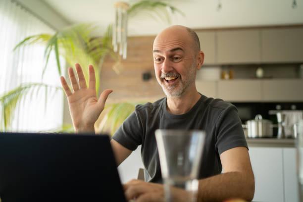 one mature adult happy smiling man phone over the internet at home during coronavirus quarantine stock photo