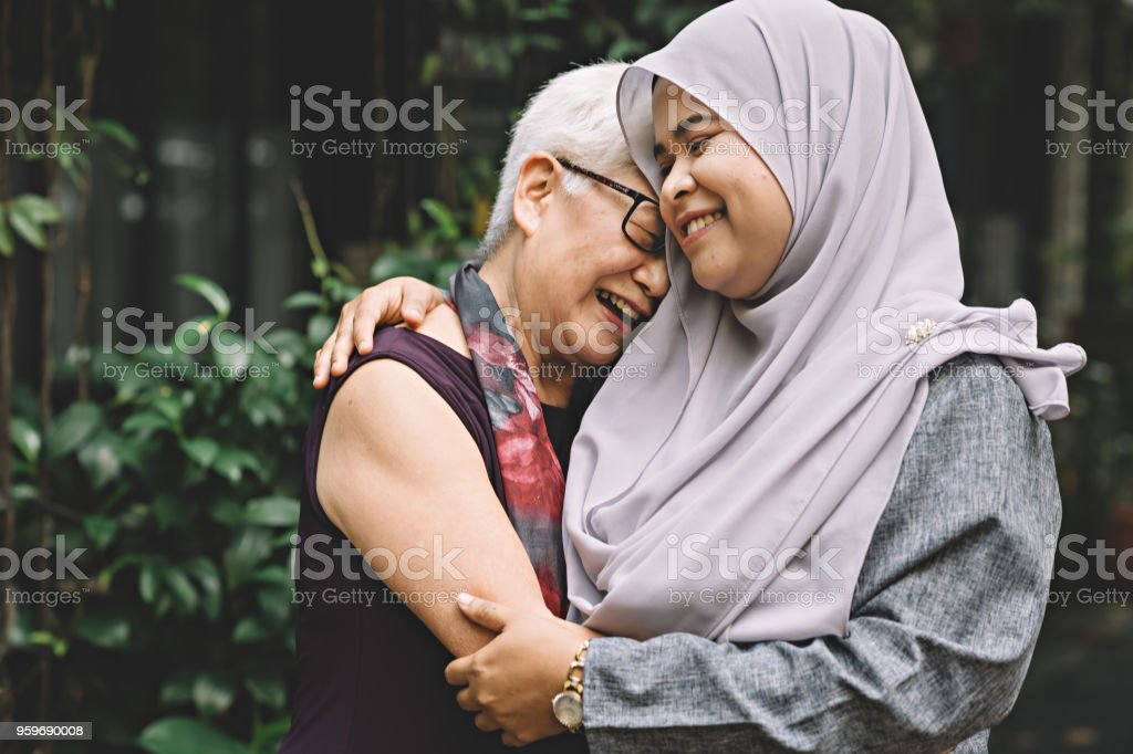 one matured asian chinese female talking and hugging a middle age asian malay female with happy expression royalty-free stock photo