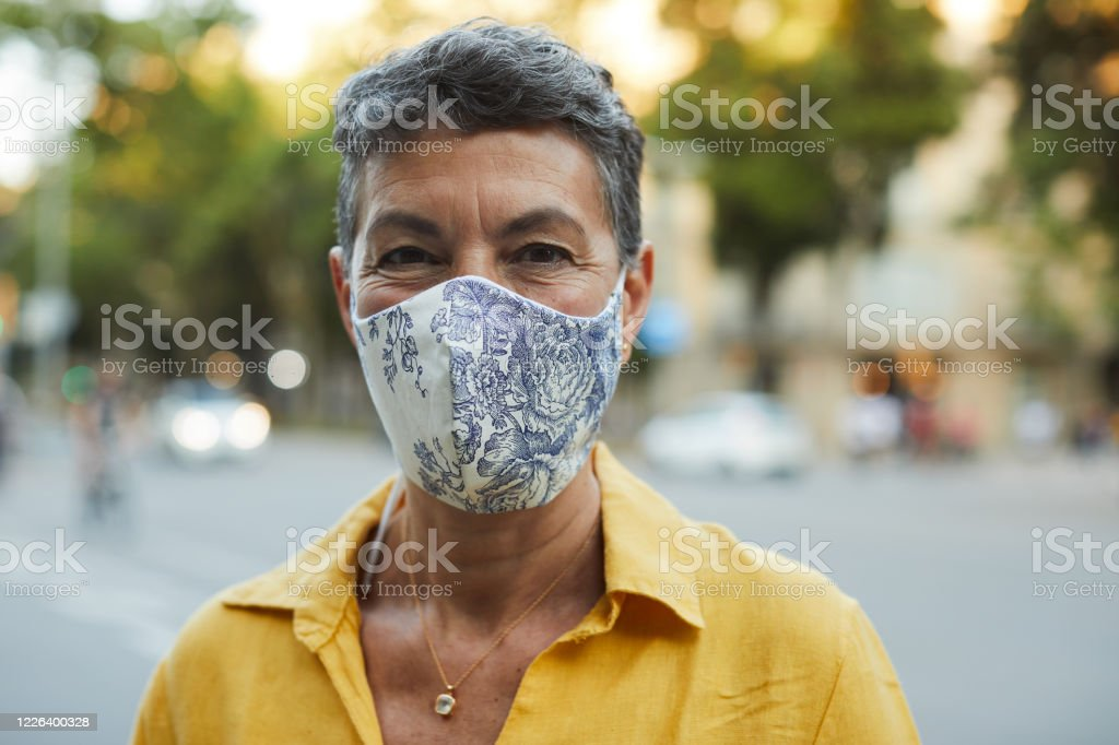 One midle aged woman wearing a protective mask and smiling One person wearing a protective mask and smiling Adult Stock Photo